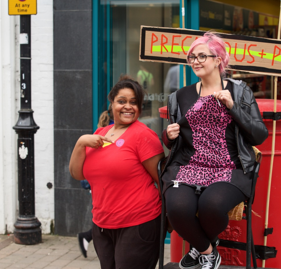 On a high street, one woman sits on a char, one woman stands next to her. They both point at badges on their chests and smile