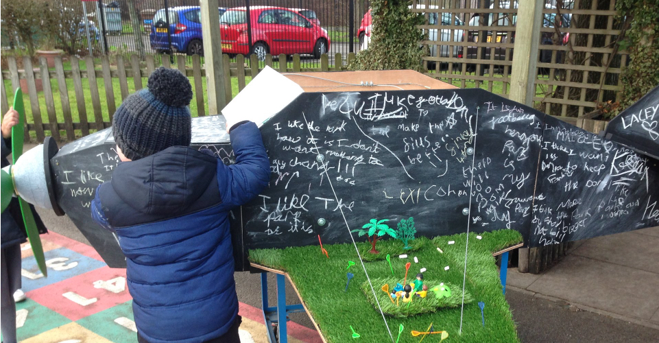 A small boy faces a five foot long model of an aeroplane. The aeroplane is covered in chalk writing and has astro-turf on its wings with model people on