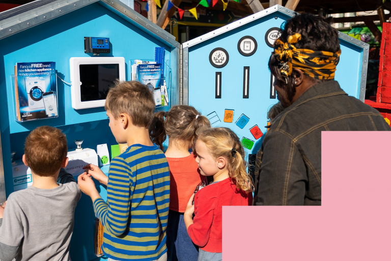 An adult and four children look at a 5 foot tall blue playable house