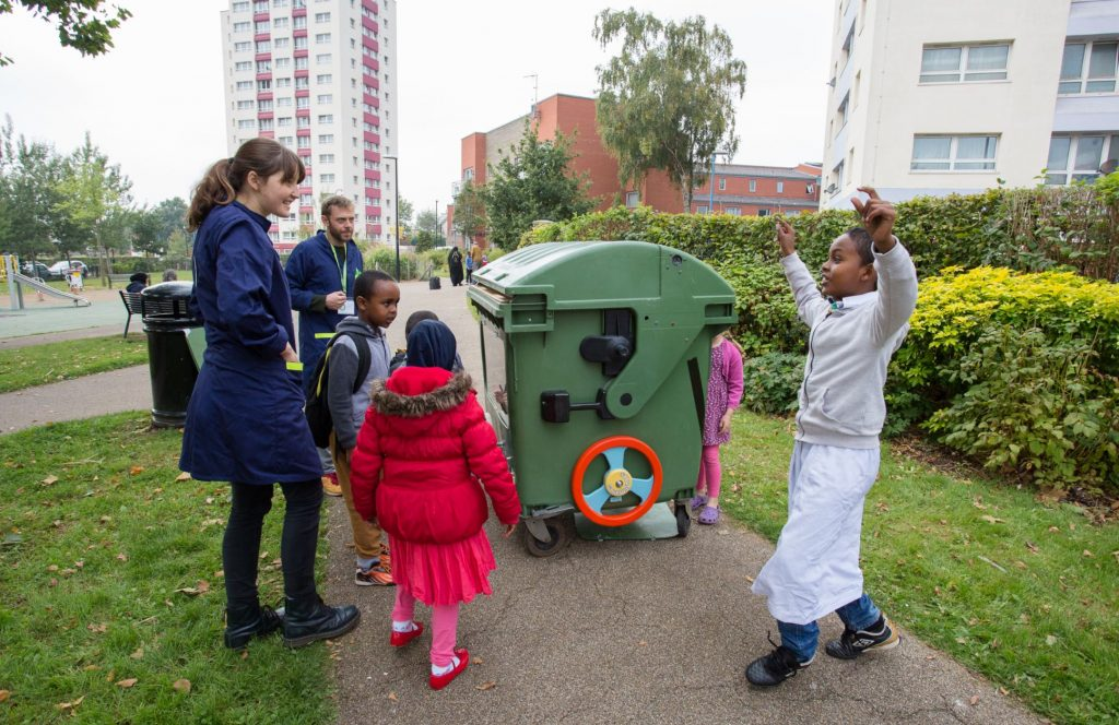 Five children and two adults stood on a path around a large green bin. One of the boys raises both arms in celebration
