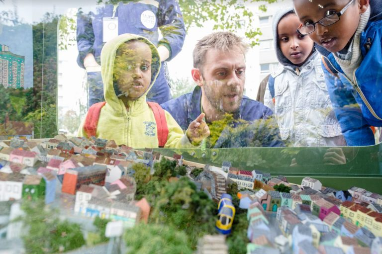 Adults and children look at a miniature model of Easton in Bristol. The model in behind plastic inside a large bin. The model is a marble run