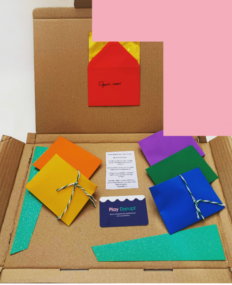 An apen cardboard box with 6 different coloured enveloped laid out. The red envelope has a gold ticket inside